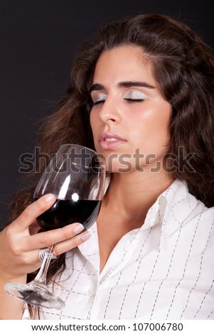 young woman smelling a glass of wine - stock photo