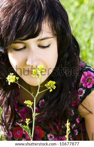 Young woman smelling yellow flower, green background - stock photo