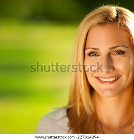 Young woman smiling and enjoying summer sunshine - stock photo