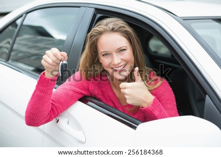 Young woman smiling and holding key in her car - stock photo