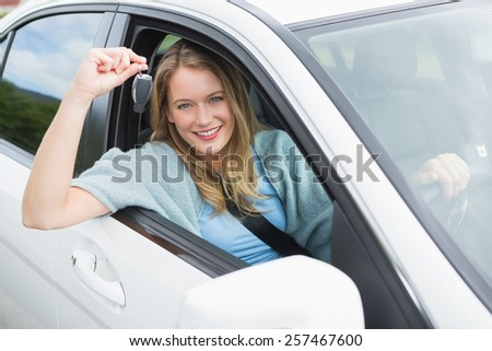 Young woman smiling and holding key in her car
