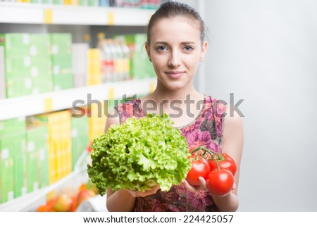Young woman smiling and holding vegetables at supermarket with shelves on background.
