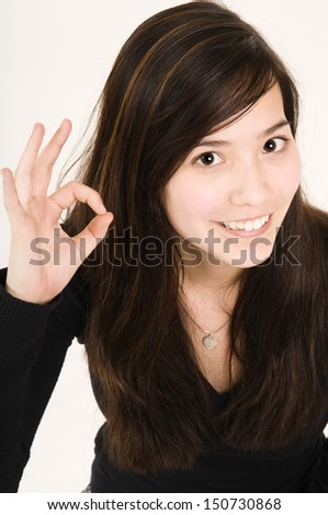 young woman smiling and show the O.K. sign; head and shoulder portrait - stock photo