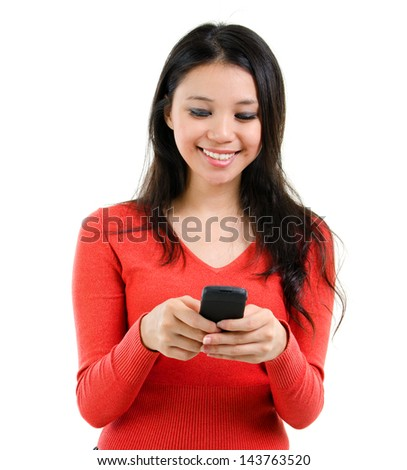 Young Woman smiling and texting on her mobile phone, isolated over white background. Mixed race Southeast Asian Caucasian girl model. - stock photo