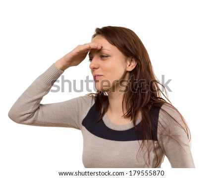Young woman smiling as she peers into the distance with her hand raised to her forehead, isolated on white - stock photo