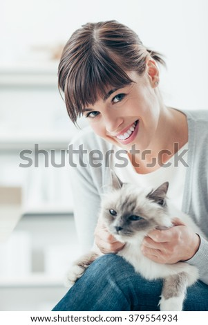 Young woman smiling at camera and caressing her beautiful birman cat on her legs - stock photo
