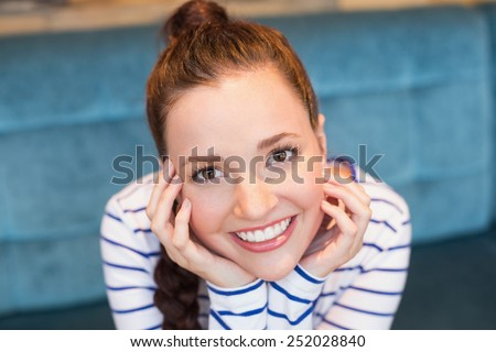 Young woman smiling at camera at the cafe - stock photo