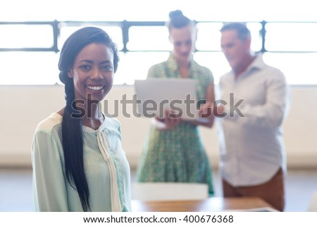 Young woman smiling at camera while colleague discuss in the background - stock photo