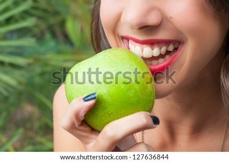 Young woman smiling holding a green apple