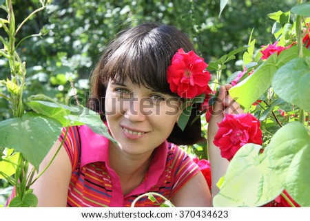 Young woman smiling in a garden among the roses.