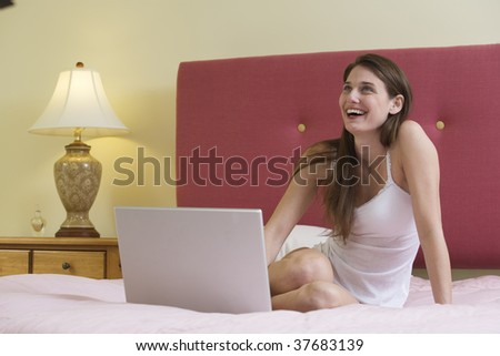 Young woman smiling in bed in front of a laptop.