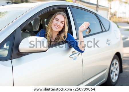 Young woman smiling in her car - stock photo