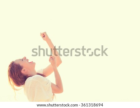 Young woman smiling looking up pumping fists celebrating freedom success. Positive human emotion face expression feeling life perception peace of mind concept. Free happy girl enjoying nature - stock photo