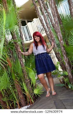 Young woman smiling posing outdoors in between some tropical palms.