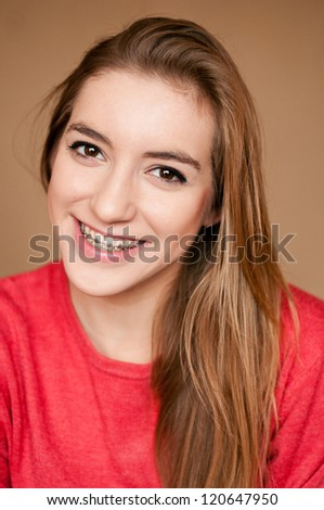 young woman smiling showing her braces - stock photo