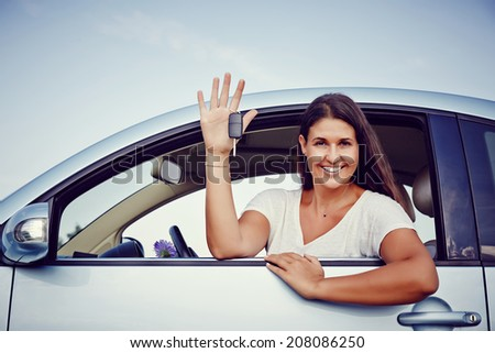 Young woman smiling showing her new car keys, keys to her rental car. - stock photo