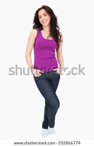 Young woman smiling the hand in her pockets against white background