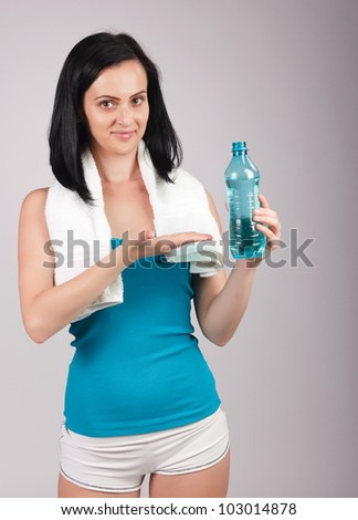 Young woman smiling to camera while promoting water bottle.Brown background. - stock photo