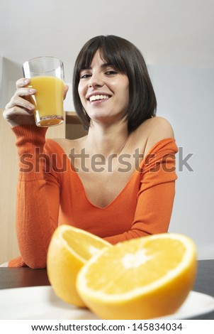 Young woman smiling while looking at glass with orange juice - stock photo