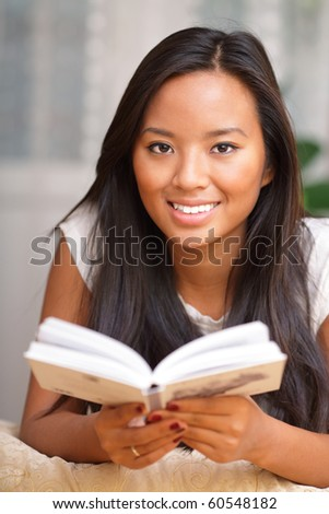 Young woman smiling while reading a book - stock photo