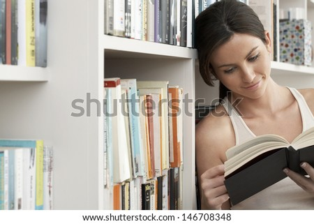 Young woman smiling while reading by bookshelves at home