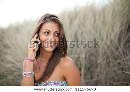 Young woman smiling while she is calling with her smart phone - stock photo