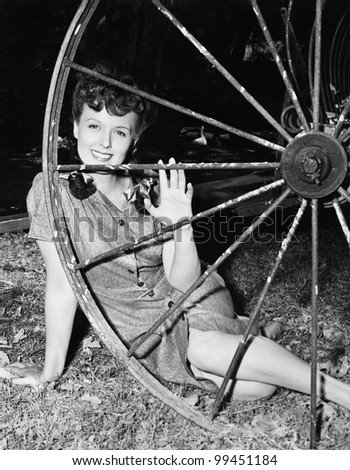 Young woman smiling while sitting behind a wagon wheel - stock photo