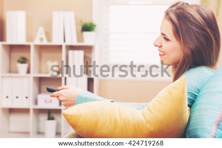 Young woman smiling while watching TV in the living room