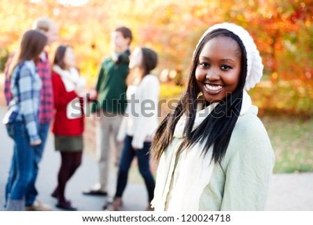 Young woman smiling with diverse friends in the background