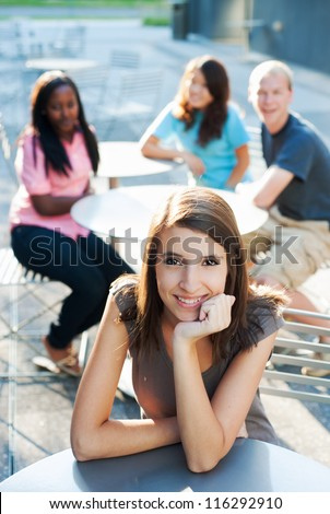 Young woman smiling with friends in the background - stock photo