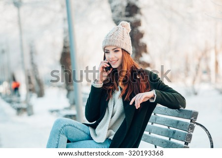 Young  woman smiling with smart phone and winter landscape  - stock photo