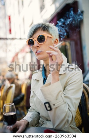Young woman smoking cigarette in a cafe in Paris, France. Shallow depth of field.  - stock photo