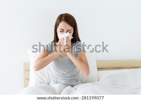 Young woman sneeze on bed