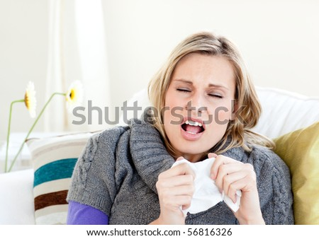 Young woman sneezes on a sofa - stock photo
