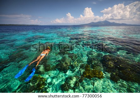 Young woman snorkeling over coral reef in transparent tropical sea. Bunaken island. Indonesia