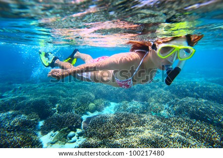 Young woman snorkeling over coral reef in tropical sea with clear transparent water - stock photo