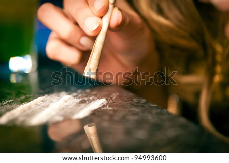 Young woman snorting cocaine with a bill, close-up - stock photo