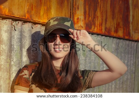 Young Woman Soldier in Camouflage Outfit Saluting - Portrait of a happy beautiful female army soldier  - stock photo