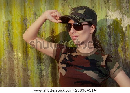 Young Woman Soldier in Camouflage Outfit Saluting - Portrait of a happy beautiful female army soldier