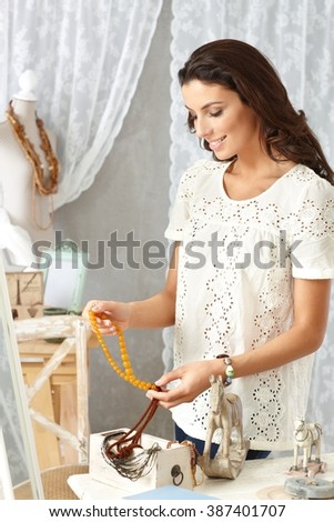 Young woman sorting accessories from wooden box at old-fashioned home, smiling.