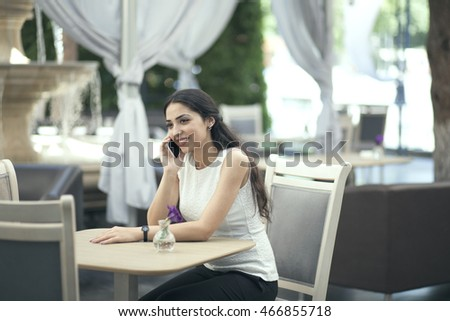 Young woman speaks by mobile phone in a cafe