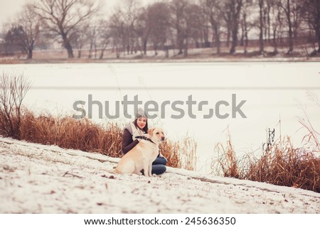 young woman spends time in the park with her dog. Girl and Labrador - stock photo
