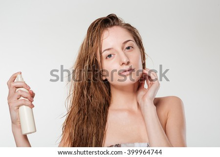 Young woman spraying hairspray isolated on a white background - stock photo