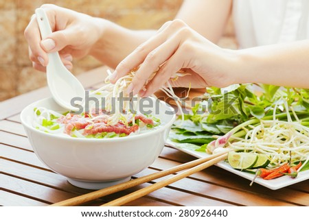 Young woman sprinkles sprouts to the Pho Bo in street cafe of Vietnam. The Pho Bo is a traditional Vietnamese beef noodle soup with garnish of leaves of cilantro and Asian basil. Popular street food. - stock photo