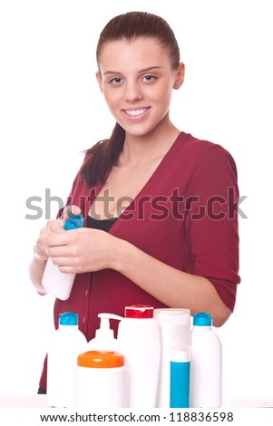 young woman squeezing the cream on his hand. in table many jars for cosmetics for skincare - stock photo