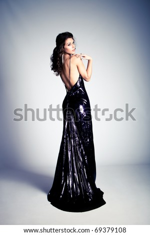 young  woman stand in red elegant dress, from back, full body shot, studio shot - stock photo