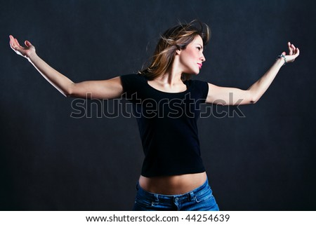 young woman stand with hands wide open, studio shot - stock photo