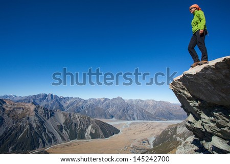 Young woman standing above mountain valley - stock photo