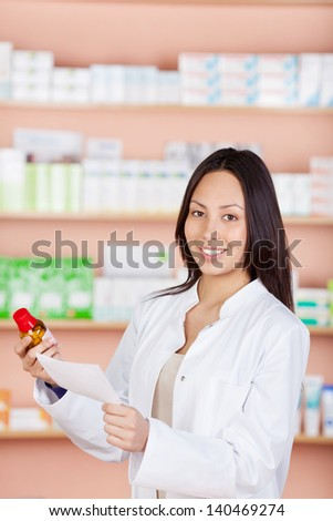 young woman standing against shelves in pharmacy - stock photo