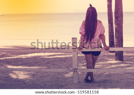 Young woman standing alone on the beach. concept lonely mood. warm tone